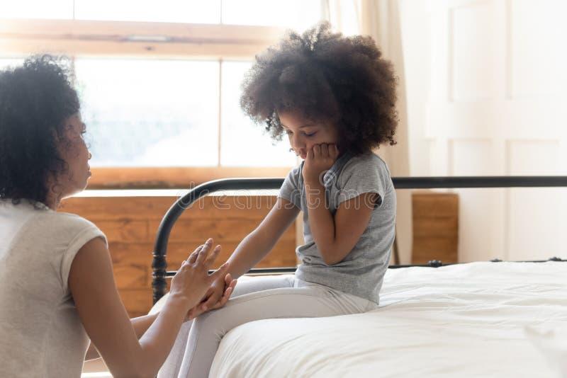 Loving biracial mom caress comfort sad little daughter stock image