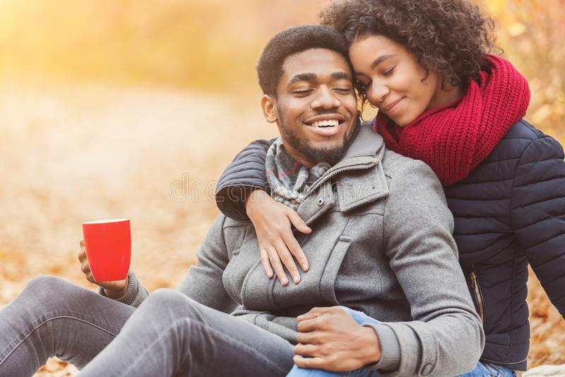 Loving african couple resting in autumn forest royalty free stock photography