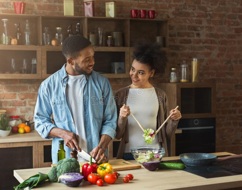 Loving afro american couple preparing green salad in kitchen royalty free stock photo