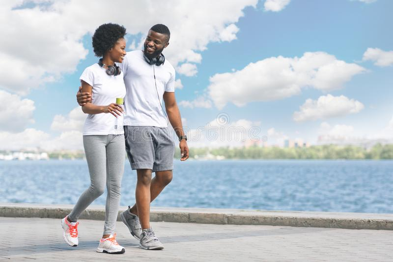 Loving Afro Couple Walking Along River Bank After Morning Jogging stock image