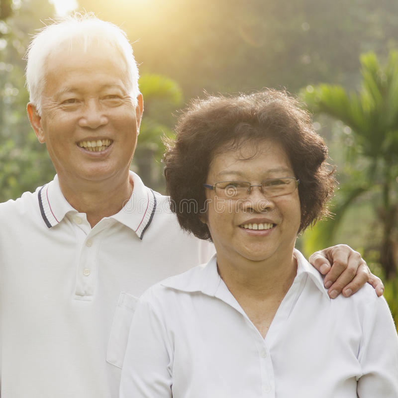 Loving Asian seniors couple outdoors. Portrait of healthy Asian seniors retiree couple relaxing at outdoor nature park, morning beautiful sunlight background royalty free stock photography