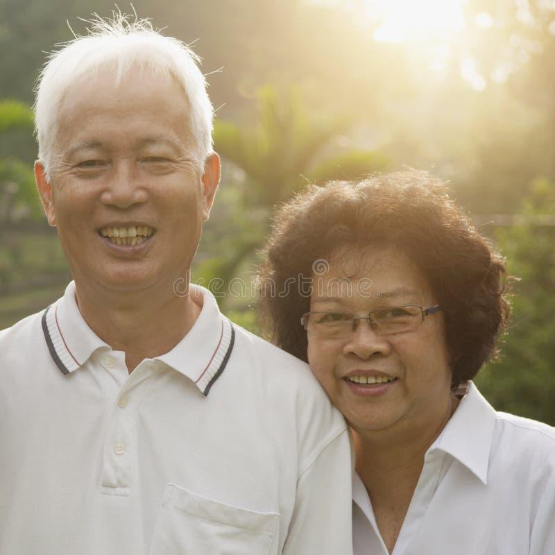 Loving Asian seniors couple. Portrait of healthy Asian seniors retiree couple enjoying life at outdoor nature park, morning beautiful sunlight background royalty free stock image