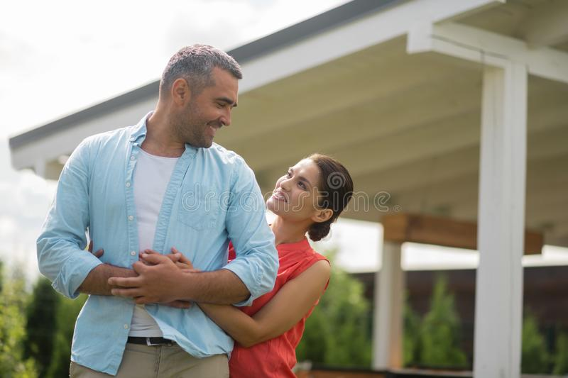 Loving beautiful wife hugging her strong handsome man. Loving wife. Loving beautiful wife smiling while hugging her strong handsome man royalty free stock photography
