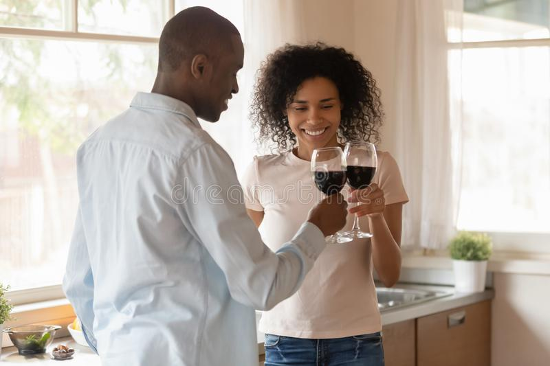 Loving biracial couple clink glasses celebrating having date. Happy african American millennial husband and wife cheers clink glasses celebrating anniversary at stock image