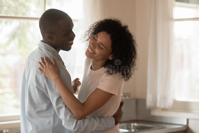 Loving biracial couple dance in kitchen celebrating anniversary. Loving happy millennial african American couple celebrate wedding anniversary dancing swaying in royalty free stock photography