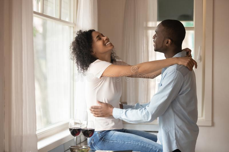 Loving biracial couple enjoy dinner date in kitchen. Happy african American young husband and wife celebrate anniversary enjoy romantic dinner with wine hug in royalty free stock images