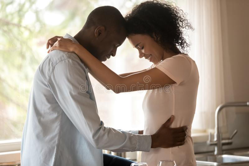 Loving biracial husband and wife touch forehead enjoy date. Loving biracial millennial husband and wife hug touch forehead enjoy close intimate moment together royalty free stock photo