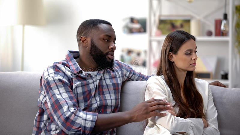 Loving black boyfriend calming girlfriend and trying to reconcile after quarrel. Stock photo stock image