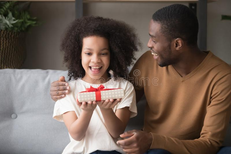 Loving black dad present gift box to happy daughter stock photo