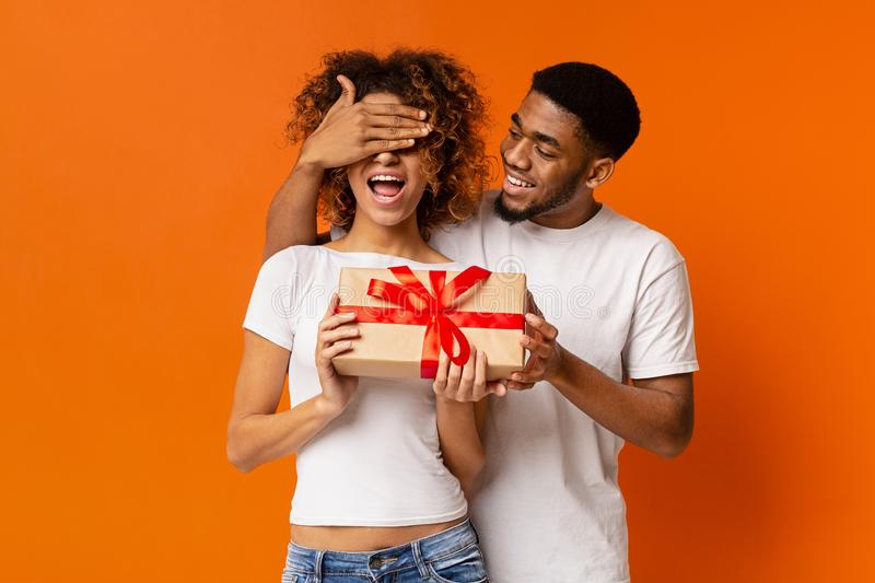 Loving black guy surprising his girlfriend with gift stock photography