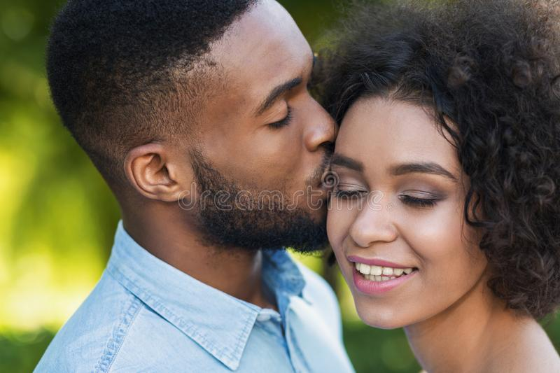 Loving black man kissing his girlfriend while walking. Loving black men kissing happy girlfriend while walking in park stock photos