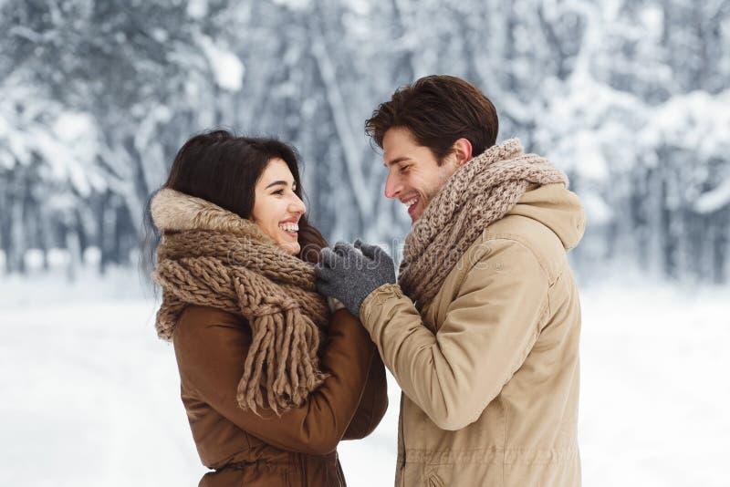 Loving Boyfriend Holding Girlfriend`s Hands Walking Outside In Snowy Forest. Winter Romance Concept. Loving Boyfriend Holding Girlfriend`s Hands Warming Her Up stock image