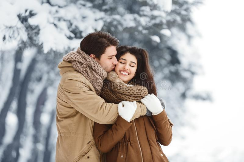 Loving Boyfriend Kissing And Hugging Girlfriend Standing In Winter Forest stock photo