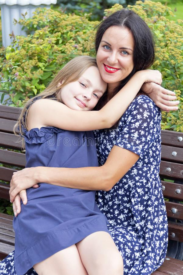 Loving brunette mother and blond daughter. Portrait of loving brunette mother and blond daughter stock photos