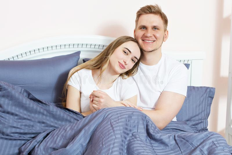 Loving caucasian couple on the bed in the bedroom. Young happy couple lying in bed and smile while look at camera royalty free stock images
