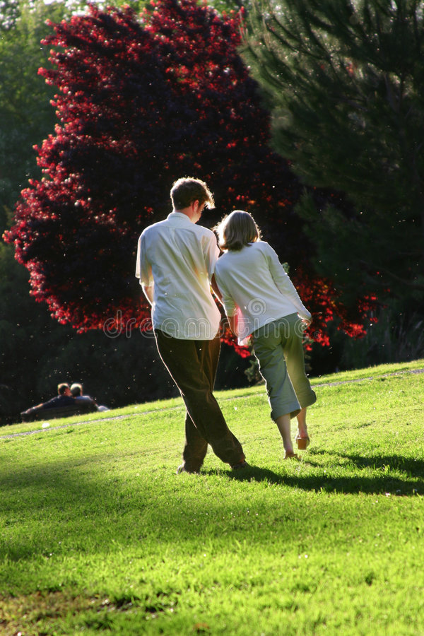 Loving Couple. Happy couple walking through park. Playful posture. (Note: The image contains little specks. These are little grass bugs that stir up when you