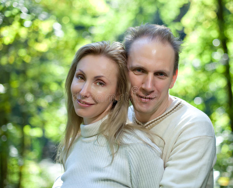 Loving Couple On A Background Of Green Foliage.Portrait In A Sunny Day Stock Photo