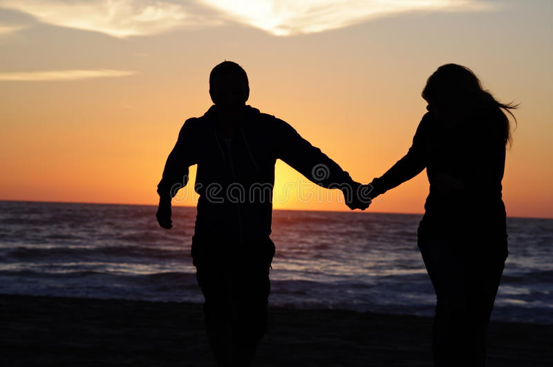 Loving couple beach sunset. A couple on the beach with sunset background royalty free stock image