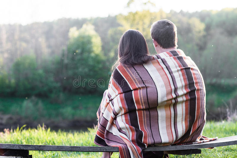 Loving couple on the bench. Loving couple sits on the bench over wonderful spring landscape stock image