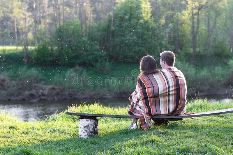 Loving couple on the bench. Loving couple sits on the bench over wonderful spring landscape royalty free stock images