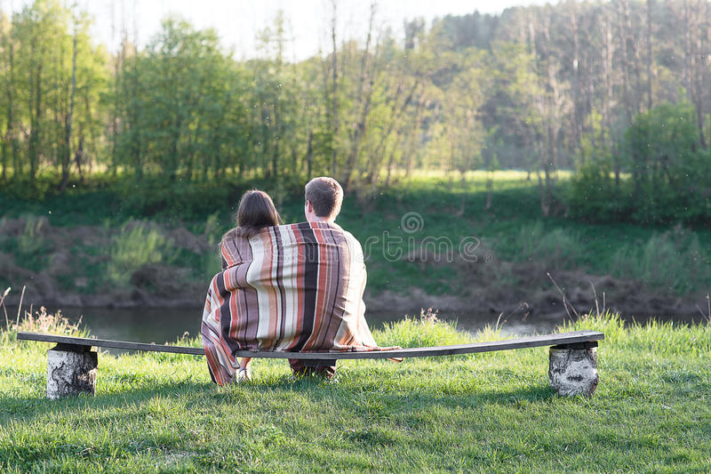 Loving couple on the bench. Loving couple sits on the bench over wonderful spring landscape royalty free stock photos