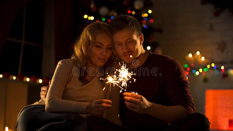Loving couple with Bengal lights sitting near Xmas tree, making wish in New Year royalty free stock photography