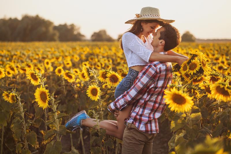 Loving couple in a blooming sunflower field royalty free stock photos