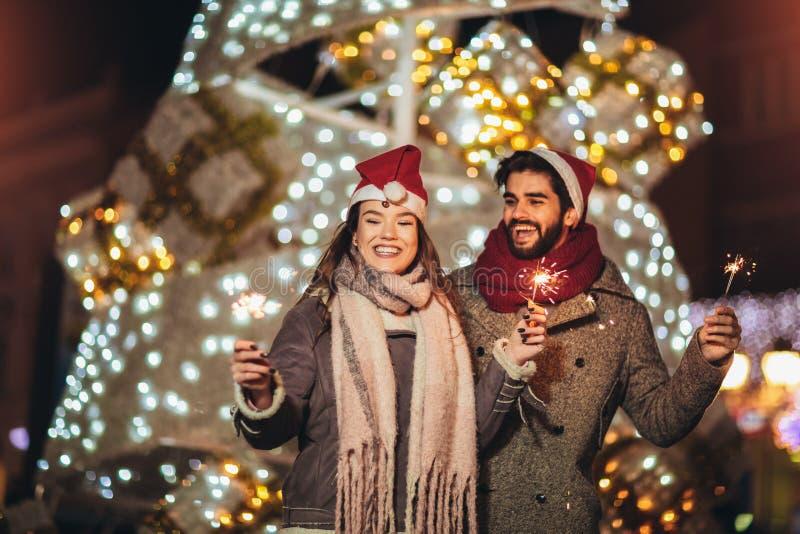 Loving couple burning sparklers by holiday illumination on new years eve stock images