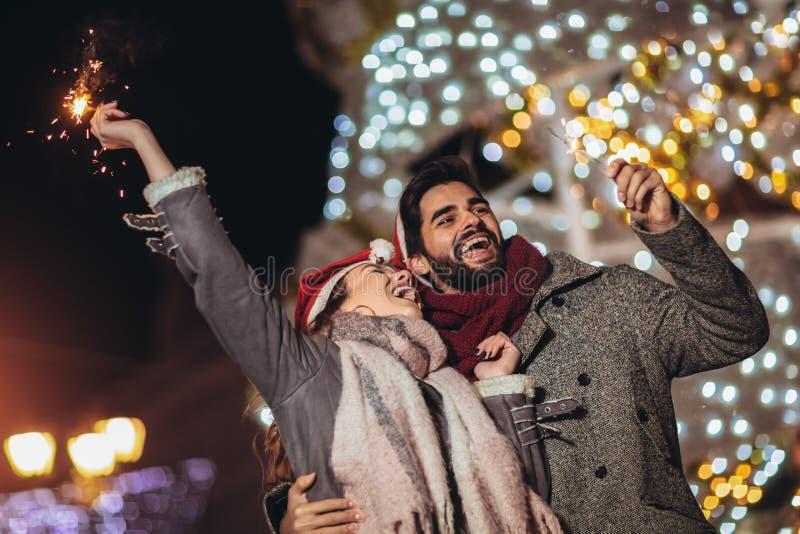 Loving couple burning sparklers by holiday illumination on new years eve stock photo