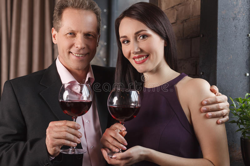 Loving couple. Cheerful middle-aged couple holding glasses with royalty free stock photo