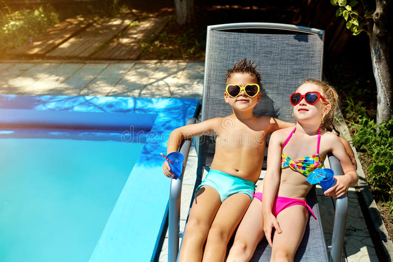 Loving couple child kids on a lounger by the pool in the summer. stock photos