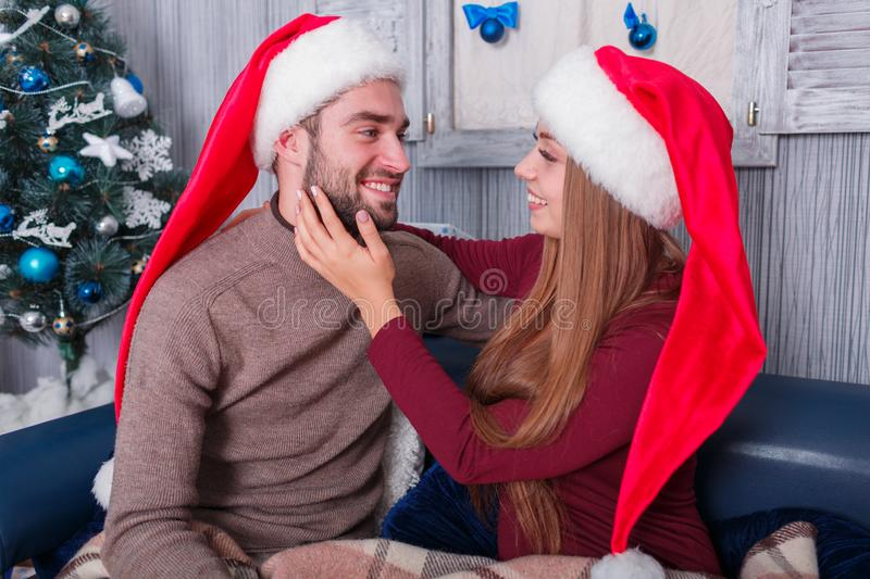 A loving couple in the red hats of the elf gently embrace and look at each other. Indoors. A loving couple in the Christmas red hats of the elf gently embrace royalty free stock photo