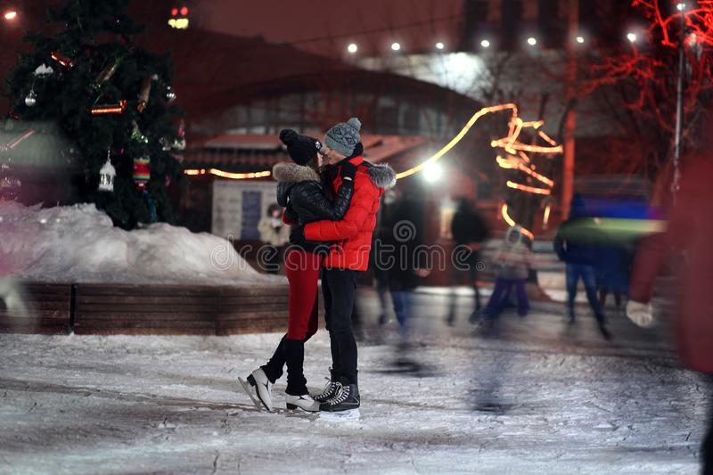 The loving couple costs an ice skating rink at night and kisses. Around the indistinct people. St. Valentine`s Day.  royalty free stock photos