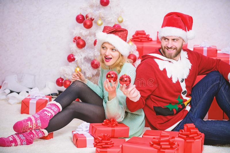 Loving couple cuddle smiling while unpacking gifts with christmas tree background. Christmas is time for giving. Couple stock photo