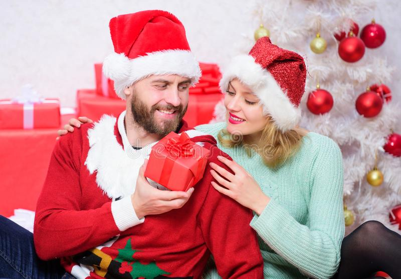 Loving couple cuddle smiling while unpacking gifts with christmas tree background. Couple in love enjoy christmas stock photo
