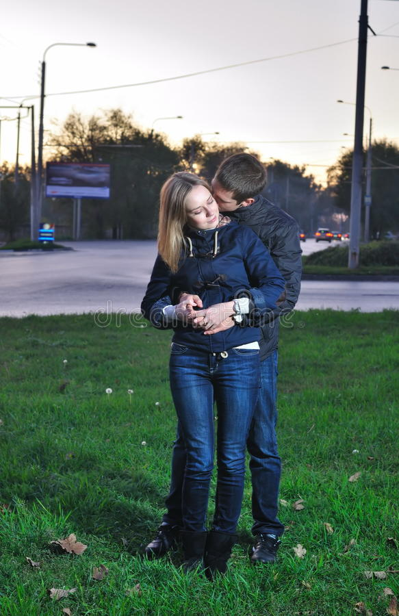 Loving couple embraces in the evening. Young pair embraces in the evening near the road royalty free stock images