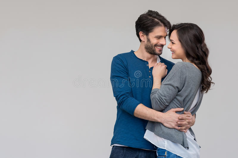 Loving couple embracing. Happy couple embracing against on gray background stock images