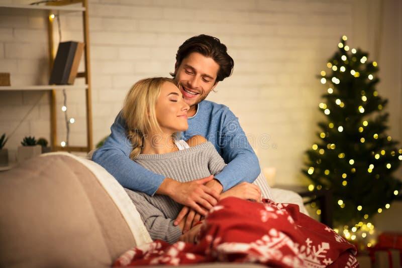 Loving couple embracing near Christmas tree, resting on sofa stock images