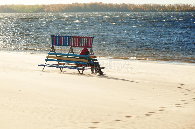 Loving couple embracing sitting on a wooden bench, enjoying the view of the river and the waves on a windy Sunny day stock photos