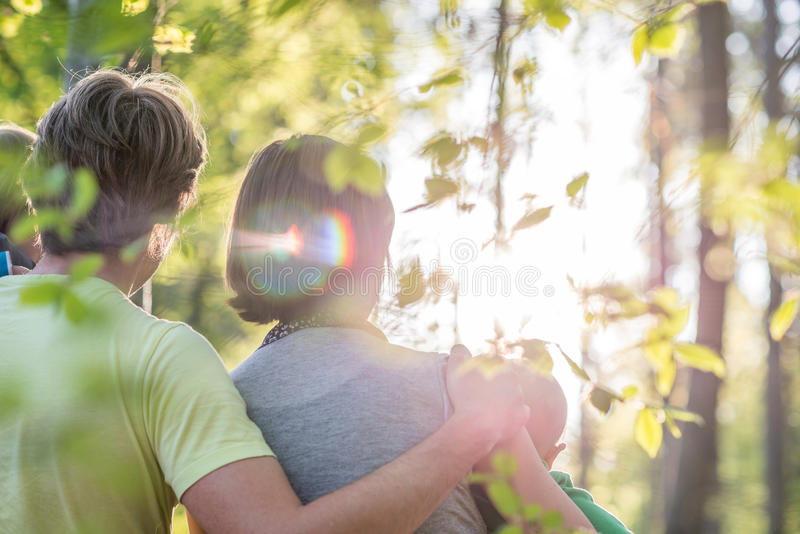 Loving couple enjoying the spring season standing arm in arm each of them holding one child. A toddler and a baby in fresh green woodland facing the rising sun royalty free stock photos