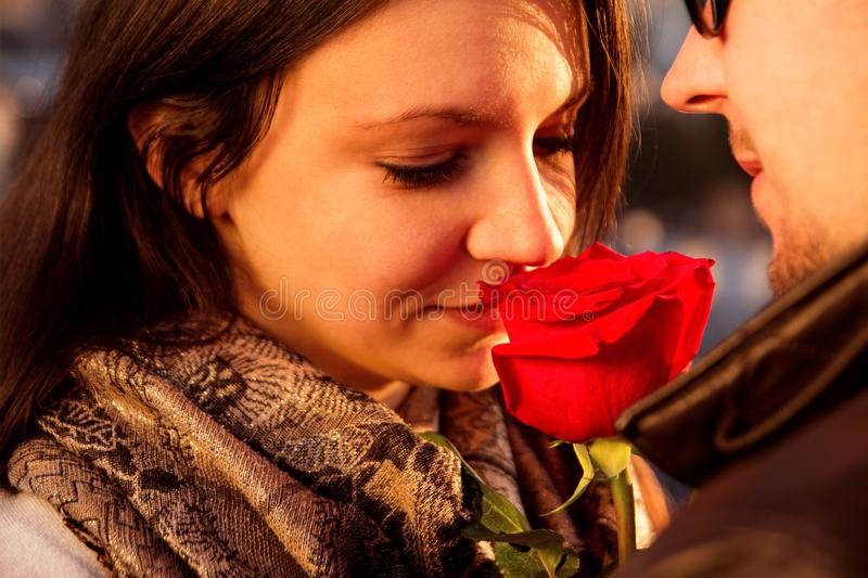 Loving couple enjoying the sun with red rose royalty free stock photography