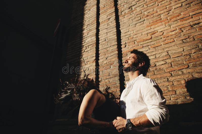Loving couple enjoying a walk in the city. Behind them is the background is a red brick wall.  royalty free stock photo