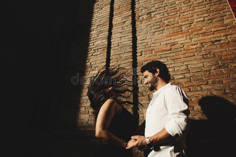 Loving couple enjoying a walk in the city. Behind them is the background is a red brick wall.  royalty free stock photos