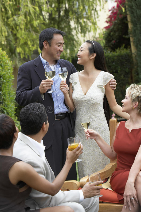 Loving Couple With Friends Toasting Drinks In Garden royalty free stock image