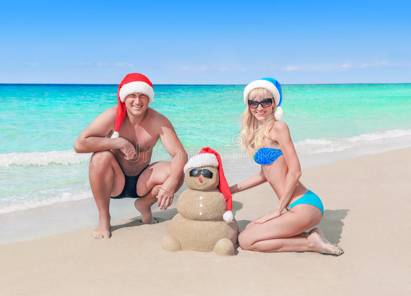 Loving couple and funny sandy Christmas snowman in santa hats at sea beach. Young cheerful couple and funny sandy snowman sculpture in santa hats at sea beach royalty free stock photography