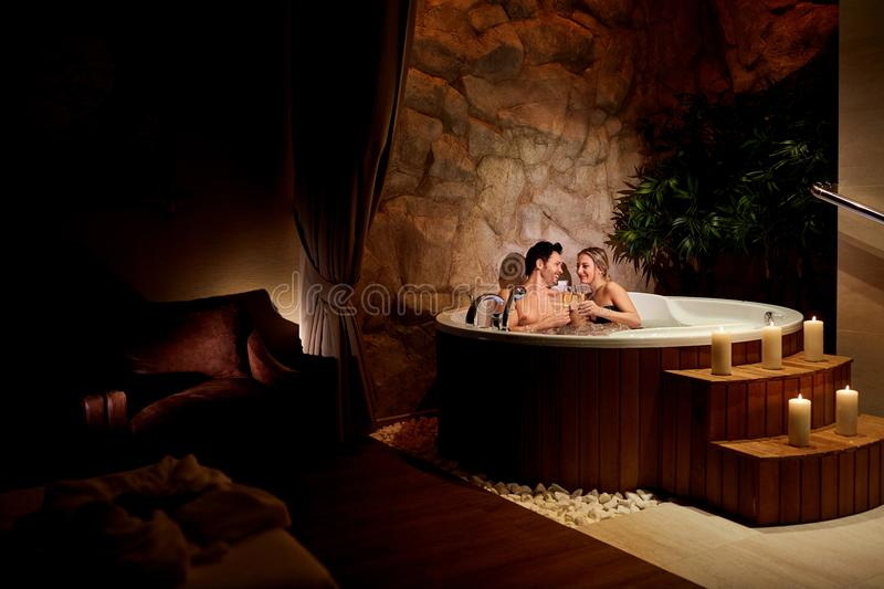 A loving couple with a glass of champagne in a jacuzzi relax. stock photo