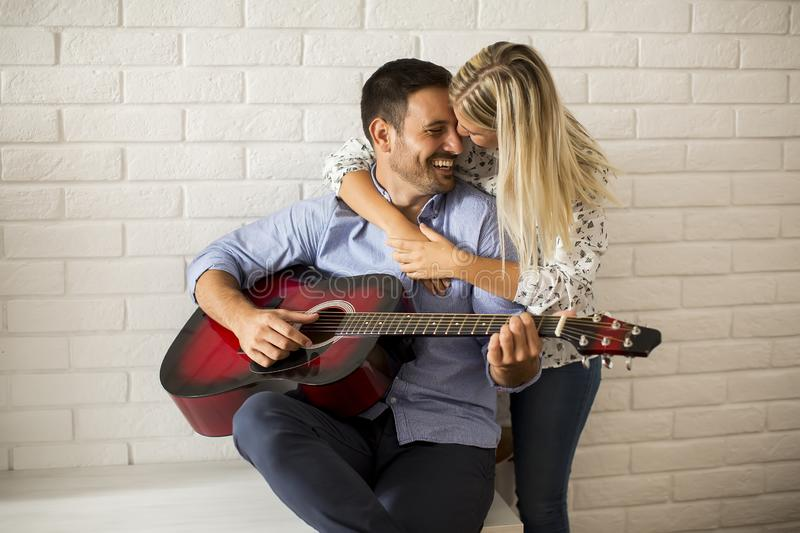 Loving couple with guitar stock photos