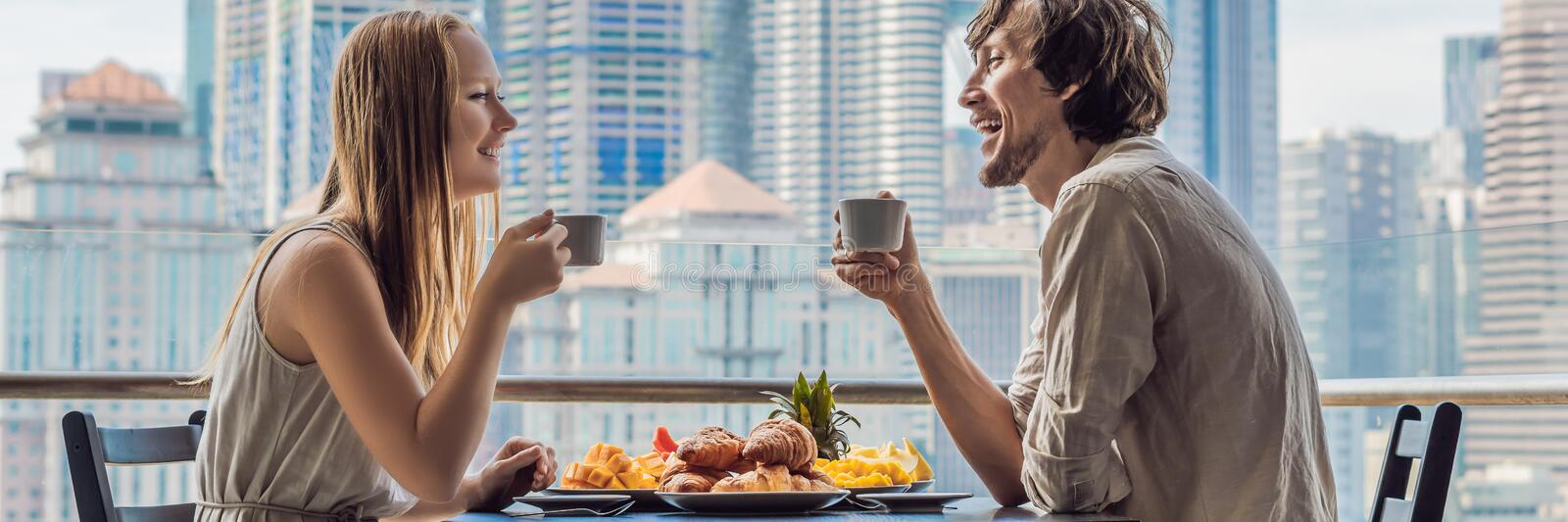 Loving couple having breakfast on the balcony. Breakfast table with coffee fruit and bread croisant on a balcony against. The backdrop of the big city. BANNER stock photo