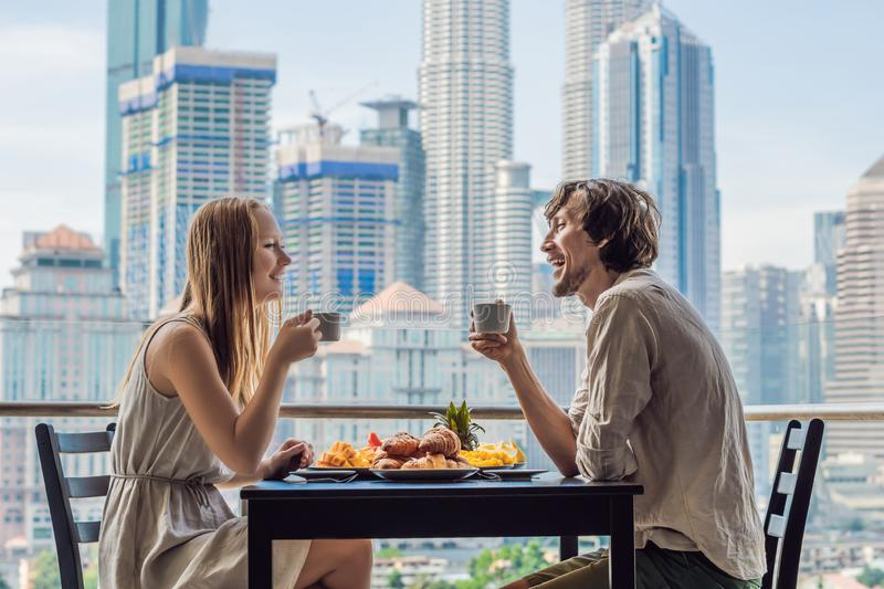 Loving couple having breakfast on the balcony. Breakfast table with coffee fruit and bread croisant on a balcony against. The backdrop of the big city stock photo