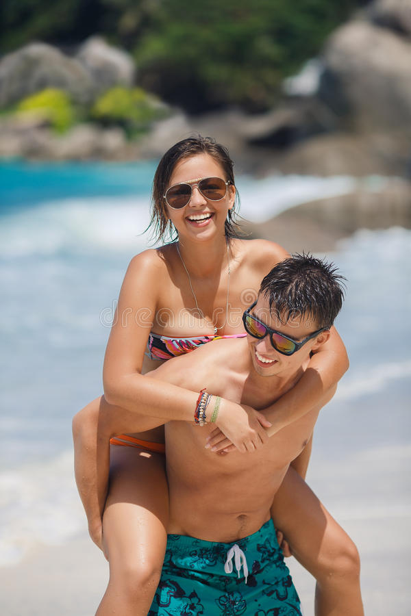 Loving couple having fun on the beach of the ocean. Happy couple piggybacking cheerful on beach during summer holidays vacation. couple in love having fun on stock photo